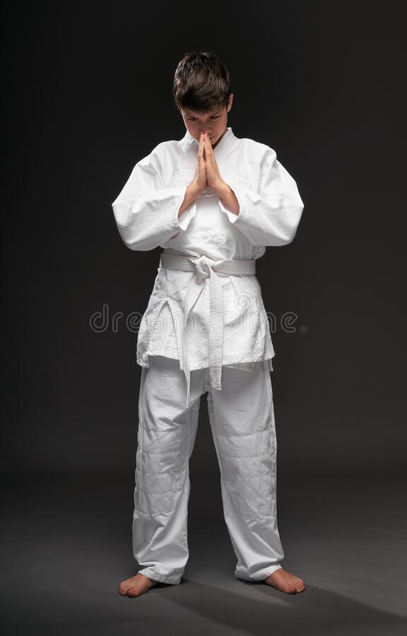 Portrait of a teenager dressed in martial arts clothing poses on a dark gray background, a sports concept royalty free stock image
