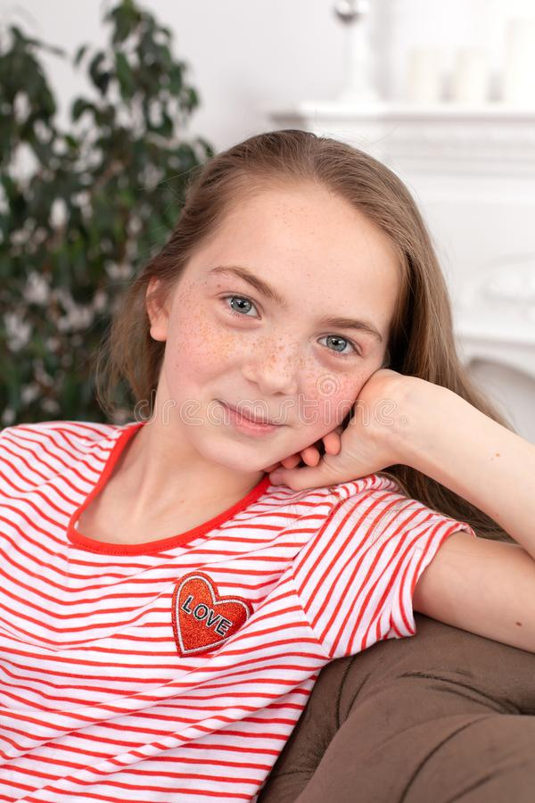 Portrait of a teenager girl with freckles sit on her favorite cozy sofa.  royalty free stock image