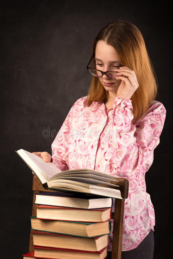 Portrait of a teenager girl reading book on stack of books. stock photos