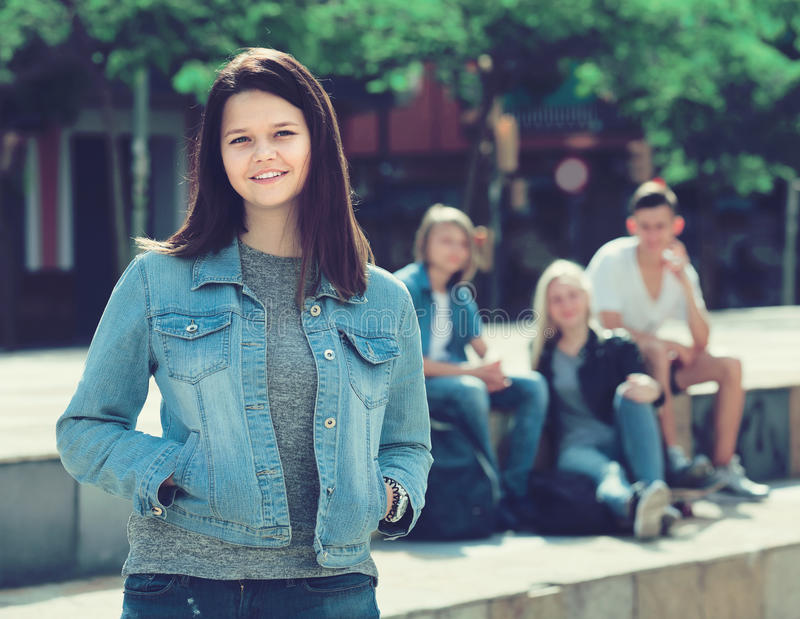 Portrait of teenager girl standing aside from friends outdoors royalty free stock images