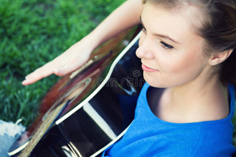 Portrait of a teenager with a guitar under a tree stock image