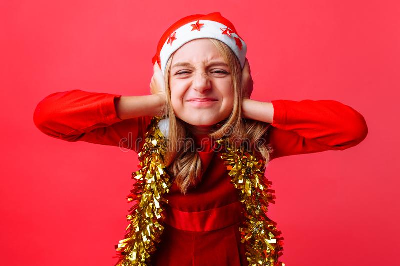 Portrait of a teenager in a Santa hat and tinsel on the neck, screaming and covering the ears of the girl, wants to hear nothing stock photos
