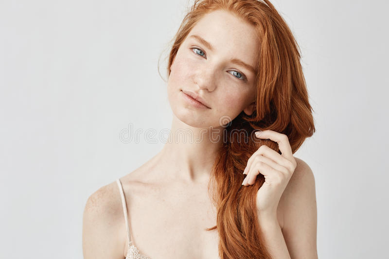 Portrait of tender beautiful girl with red hair smiling looking at camera. Portrait of tender beautiful girl with red hair smiling looking at camera over white royalty free stock images