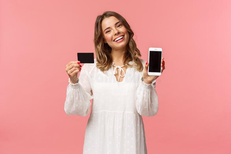Portrait of tender feminine young blond girl in white dress, tilt head and smiling pleased, advice download application. Holding mobile phone, credit card royalty free stock images