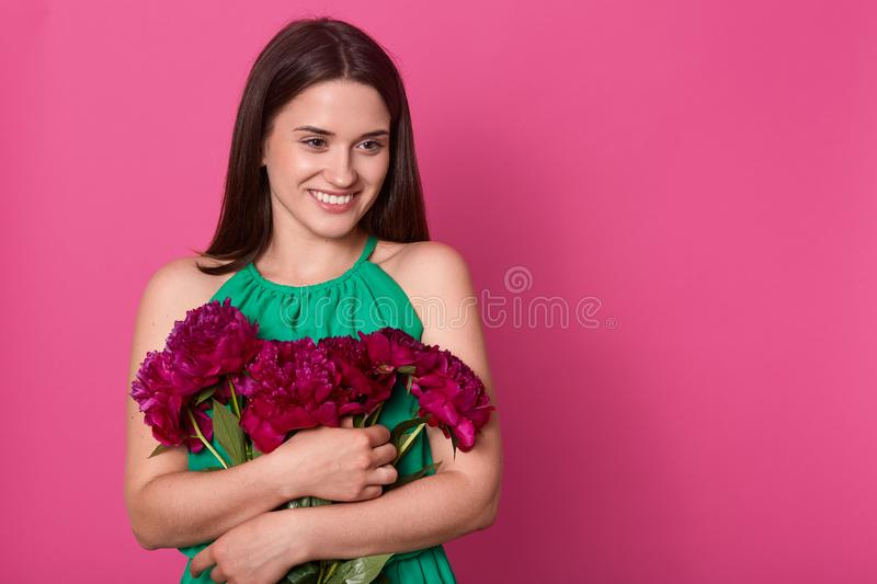 Portrait of tender positive young girl looking aside, keeping close bunch of flowers, enjoying bouquet of dark pink peonies, being stock photos
