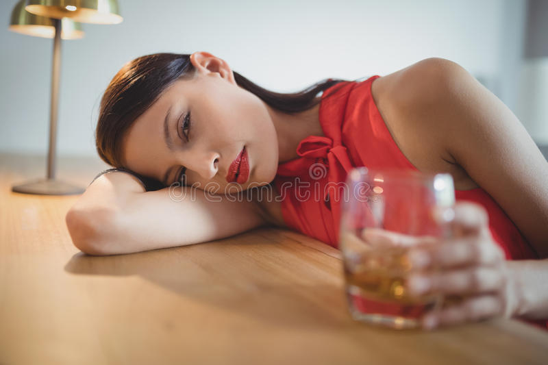 Portrait of tensed woman having a glass of whisky royalty free stock photography
