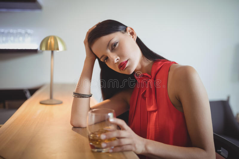 Portrait of tensed woman having a glass of whisky stock image