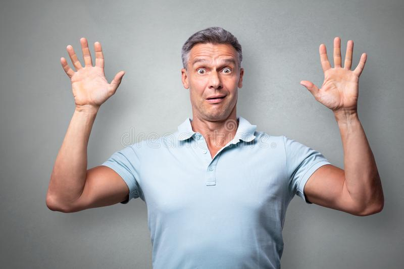 Portrait Of A Terrified Man. Against Grey Background stock photos