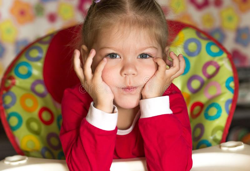 Portrait of thinking and sad little girl propping head by hands royalty free stock photo