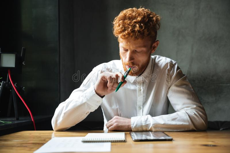 Portrait of thinking young readhead man in white shirt, sitting royalty free stock photo