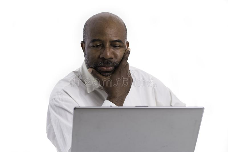 Portrait of thoughful and pensive African American software expert sitting front of a laptop computer.   Contemplating man working stock photo