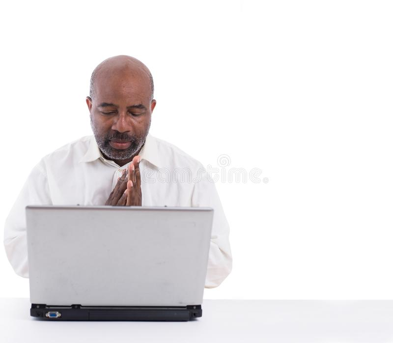 Portrait of thoughful and pensive African American software expert sitting front of a laptop computer.   Contemplating man working royalty free stock photography