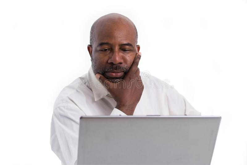 Portrait of thoughful and pensive African American software expert sitting front of a laptop computer.   Contemplating man working royalty free stock photos