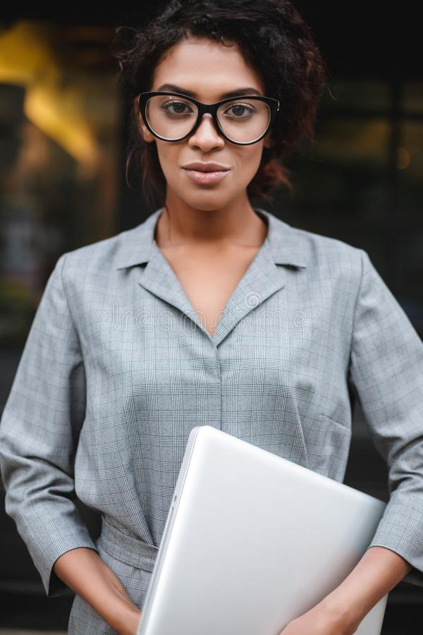 Thoughtful African American girl in glasses standing with laptop in hand and dreamily looking in camera. Young lady with. Portrait of thoughtful African American royalty free stock photography