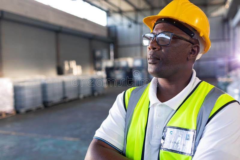 Male staff in hardhat and reflective jacket standing with arms crossed in warehouse royalty free stock photo