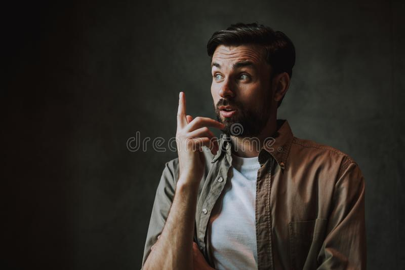 Pensive unshaven male brainstorming and flourishing hand royalty free stock images