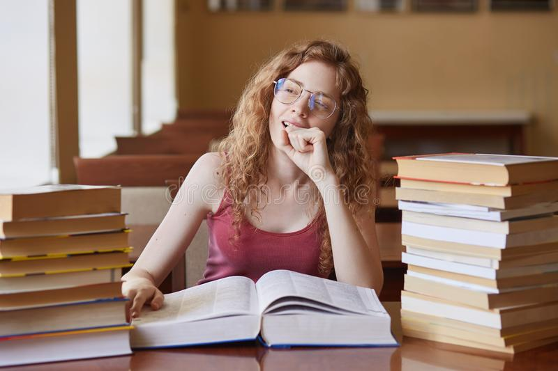 Portrait of thoughtful dreamy young student sitting in reading hall, putting her hand close to face, touching huge opened book, stock photo