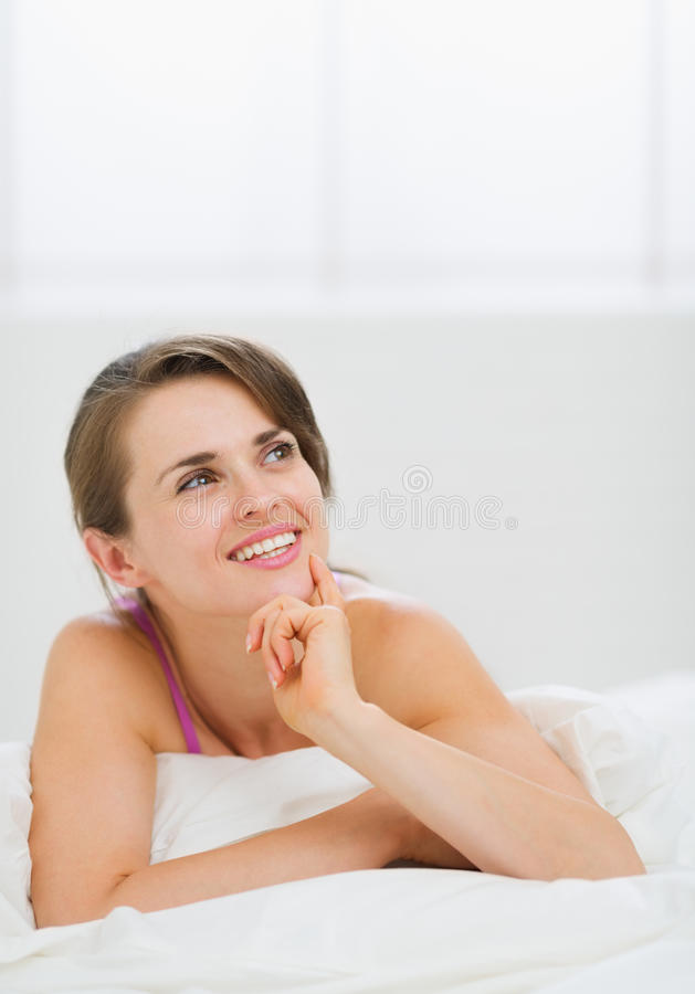 Portrait of thoughtful girl laying on bed stock image