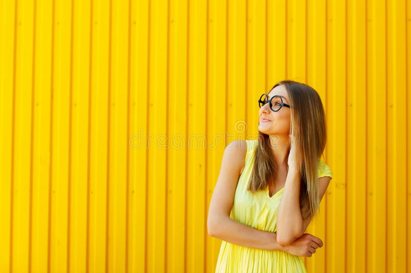 Portrait of a thoughtful girl wearing glasses looking up over ye royalty free stock image