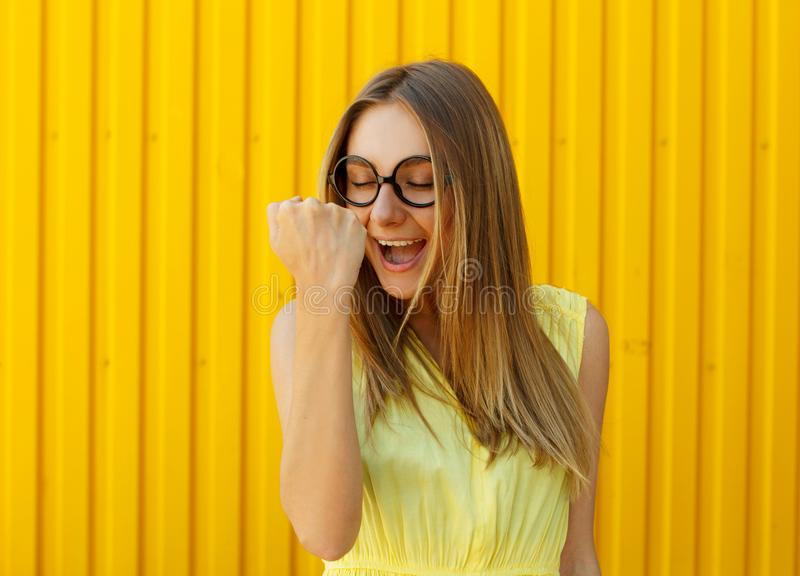 Portrait of a thoughtful girl wearing toy funny glasses celebrating her success over yellow background royalty free stock images