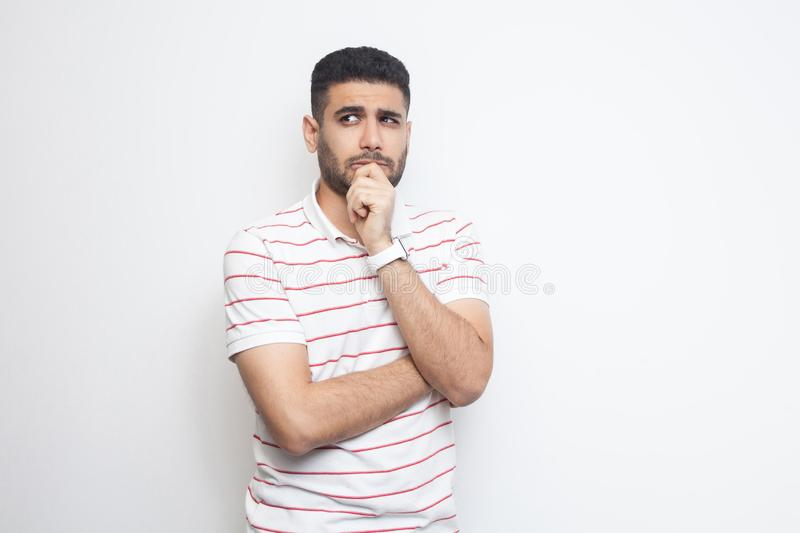 Portrait of thoughtful handsome bearded young man in striped t-shirt standing, looking away and thinking what to do royalty free stock photo