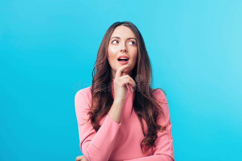 Portrait of thoughtful happy woman looking sideways isolated on blue background royalty free stock photos