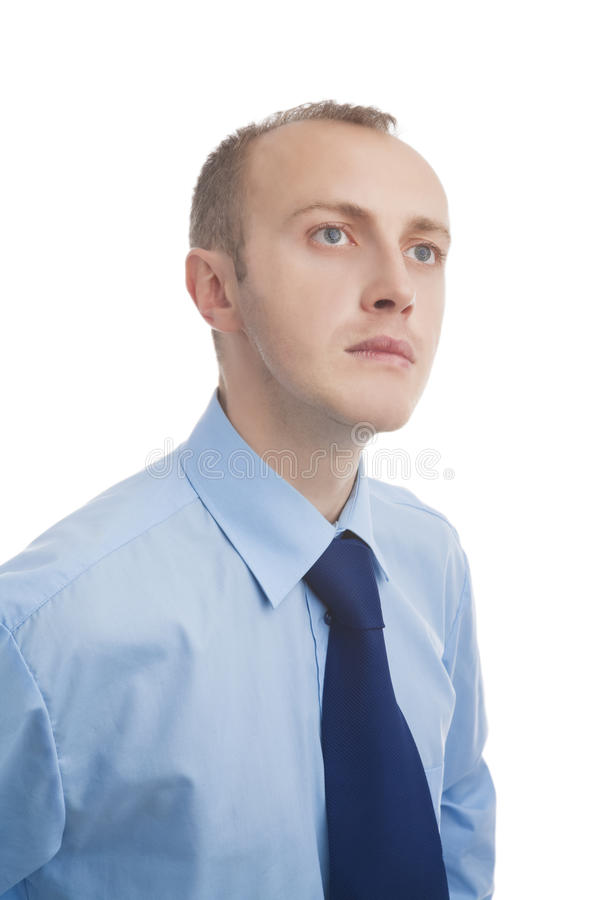 Portrait of a thoughtful man. Standing in blue shirt against white stock image