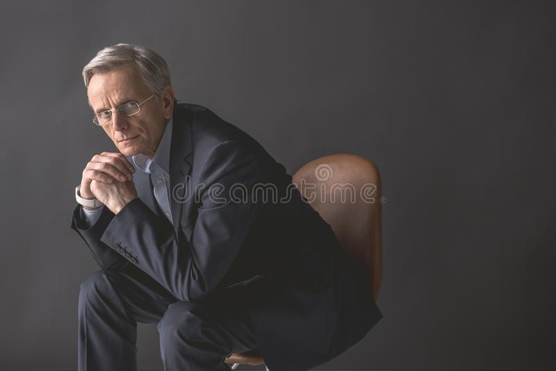 Pensive old businessman locating on chair royalty free stock photos