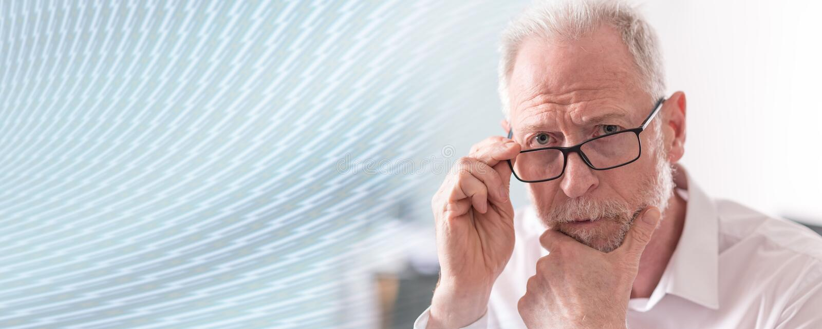 Thoughtful senior businessman; panoramic banner stock photo