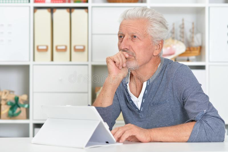 Portrait of thoughtful senior man with tablet stock image