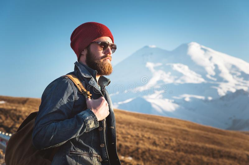 Portrait of a thoughtful stylish hipster with a beard in sunglasses and a hat with a backpack on the background of the royalty free stock photos
