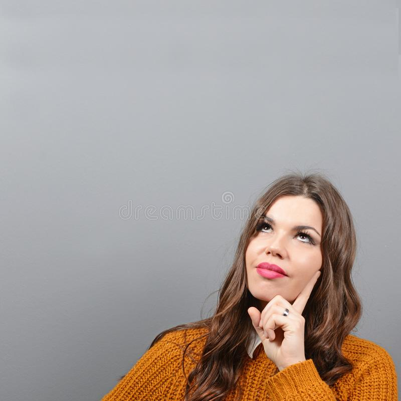 Portrait of thoughtful woman against gray background stock photo