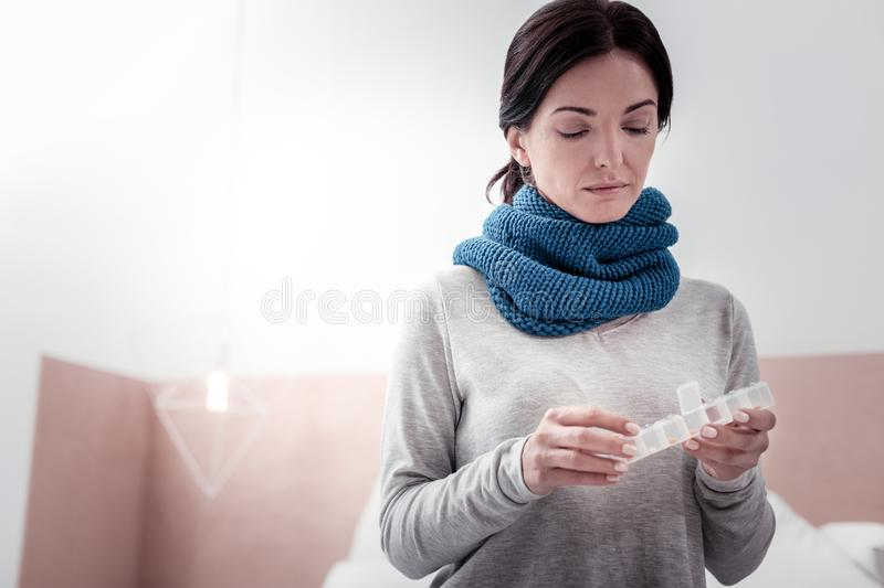 Portrait of thoughtful woman holding a box with pills royalty free stock image