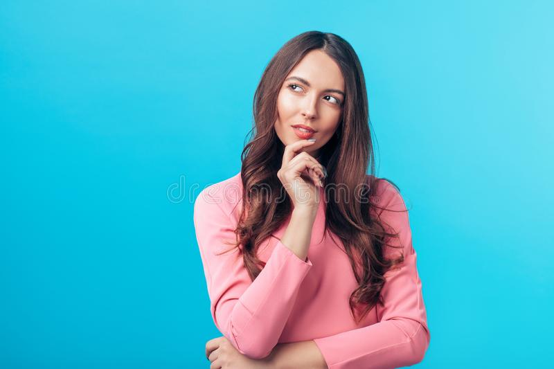 Portrait of thoughtful wondering woman looking sideways isolated over blue background stock photo