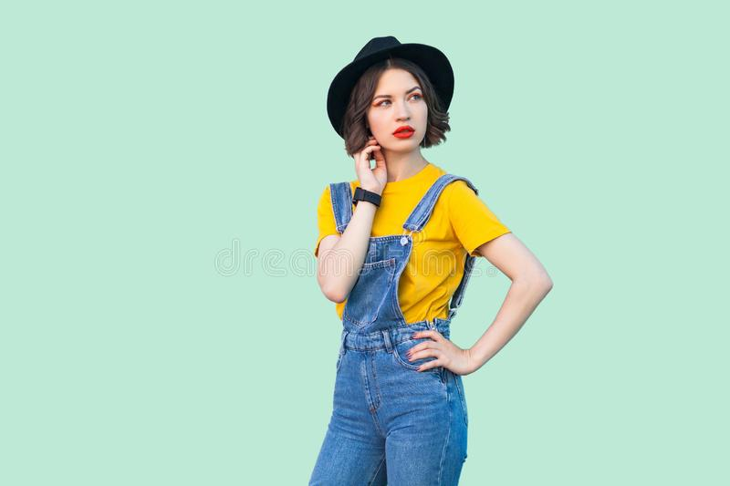 Portrait of thoughtful young hipster girl in blue denim overalls, yellow shirt, black hat standing wit hand on waist, looking away. And thinking. indoor studio stock photo