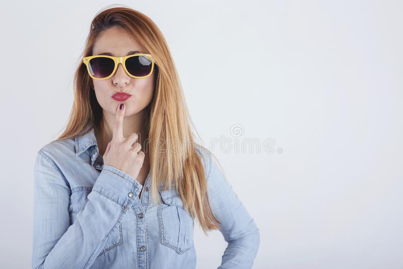 Portrait of thoughtful young woman with sunglasses. On white background royalty free stock image