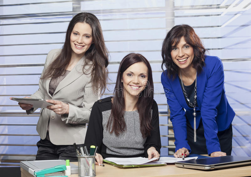 Portrait of a three attractive female colleagues. In the office royalty free stock photo