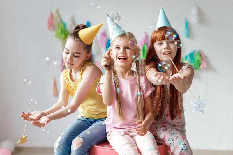 Portrait of three beautiful girls wear festive caps, play with bubbles, sit together on chair, celebrate birthday, being. In good mood, use magic wand, have stock photo