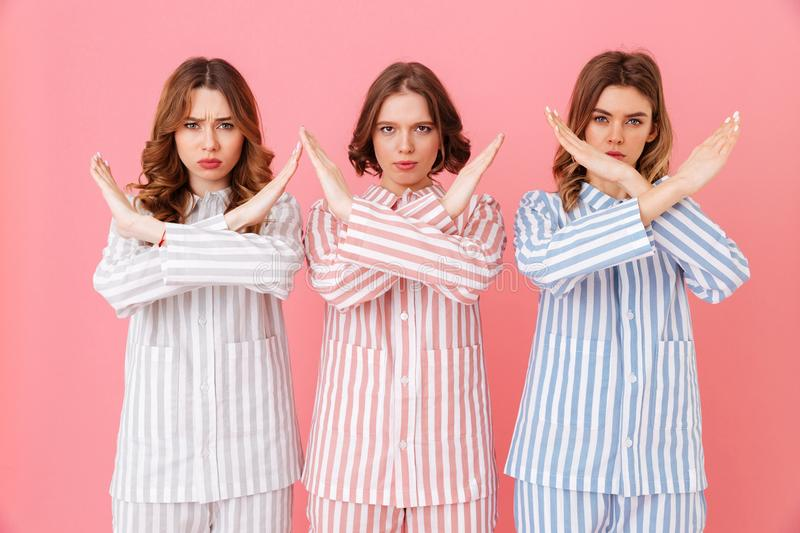 Portrait of three beautiful young girls 20s wearing colorful striped pyjamas showing crossed hands no gesture meaning deny. At home party isolated over pink royalty free stock images