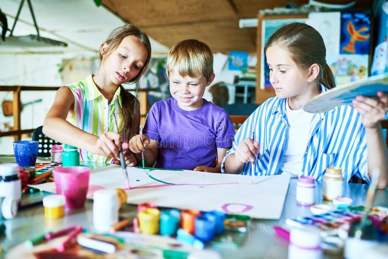 Children Painting in Art Class. Portrait of three children painting picture together smiling happily while working in art studio during lesson royalty free stock image