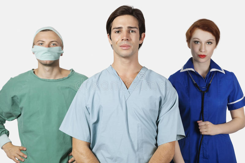 Portrait of three confident medical practitioners against gray background royalty free stock photography