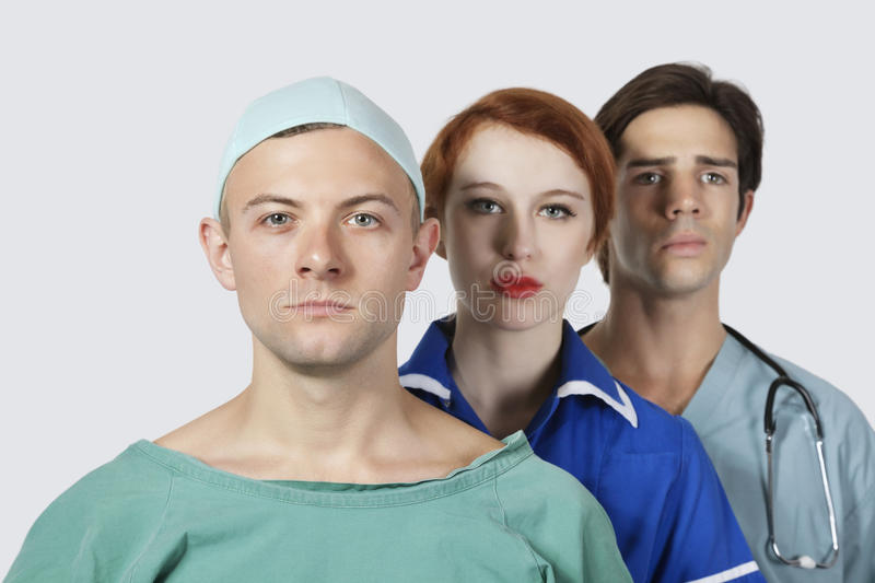 Portrait of three confident medical practitioners against gray background royalty free stock photos