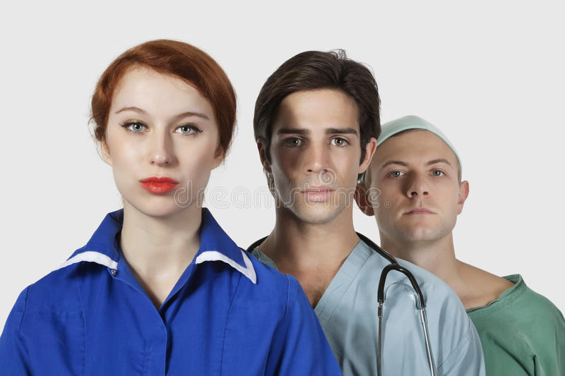 Portrait of three confident medical practitioners against gray background stock photography