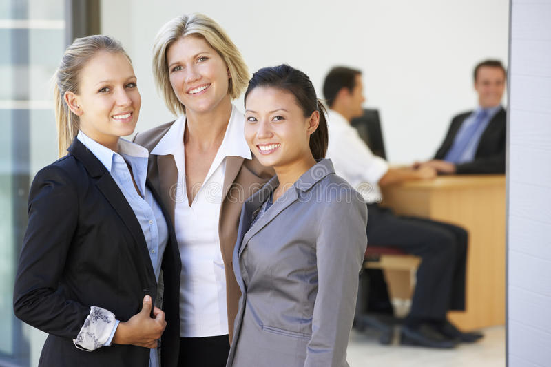 Portrait Of Three Female Executives With Office Meeting In Background royalty free stock photo