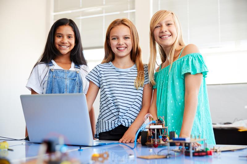 Portrait Of Three Female Students Building And Programing Robot Vehicle In School Computer Class stock image