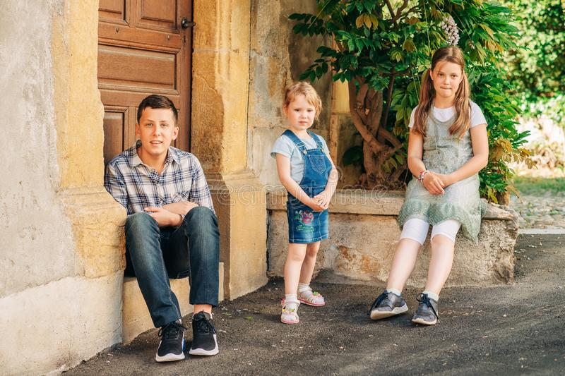 Portrait of three funny kids posing outdoors. Portrait of three funny kids posing outdoor, teenage boy with little sisters, happy family stock photo