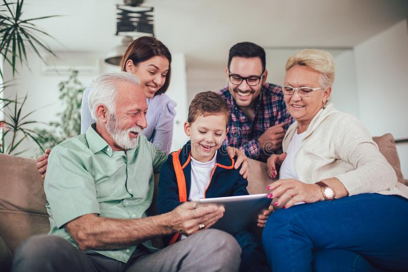 Three generation family spending time together at home using digital tablet stock photos