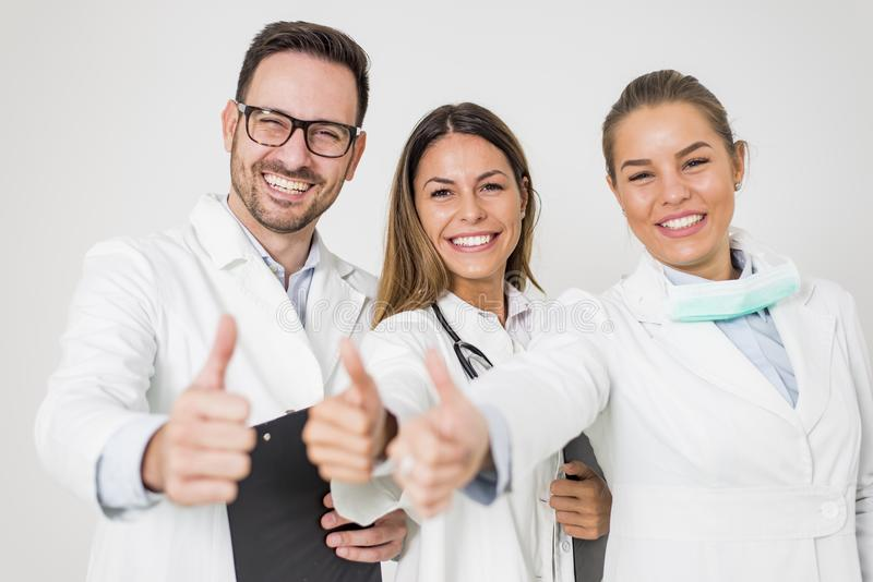 Portrait of three happy doctors who stand smiling and show thumb stock image