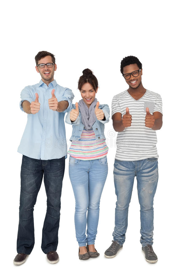 Portrait Of Three Happy Friends Gesturing Thumbs Up Stock Photo