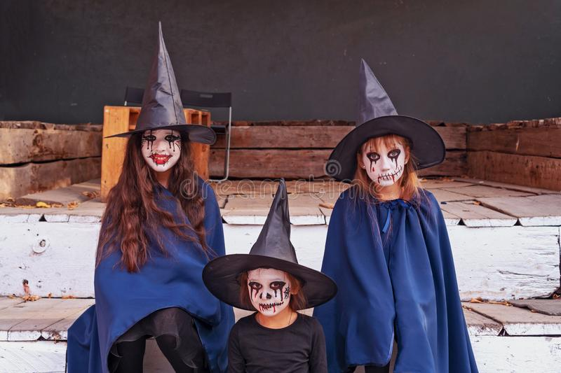 Portrait of three little cute girls in witch costumes on the background of an old and abandoned building. Halloween concept. Toned royalty free stock photo